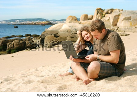 man and woman working with computer at beach - stock photo