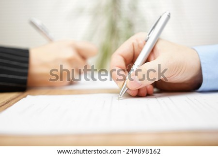 man and woman writing on document - stock photo