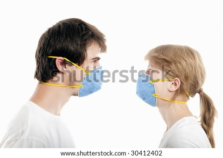 Man and woman 20-35 years  wearing  blue face masks  and looking one to another - stock photo