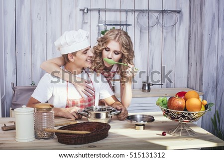 Man and woman young and beautiful couple in the kitchen home cook and have Breakfast together, helping each other