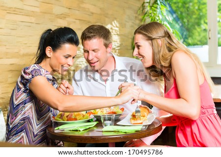 Man and women, perhaps colleagues or friends eating together healthy lunch or breakfast and taste from each others plate