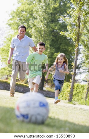 Man and young boy and girl outdoors playing soccer and having fun - stock photo
