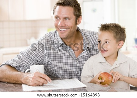 Man and young boy in kitchen with newspaper apple and coffee smiling - stock photo