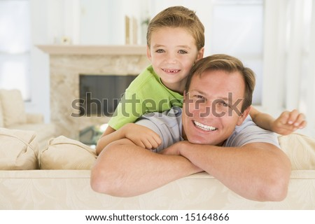 Man and young boy sitting in living room smiling - stock photo