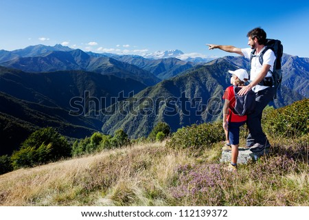 Man and young boy standing in a mountain meadow. The man points to a direction, showing something to the boy. Summer season, clear blue sky. Monte Rosa Massif, Piemonte, west italian Alps. - stock photo