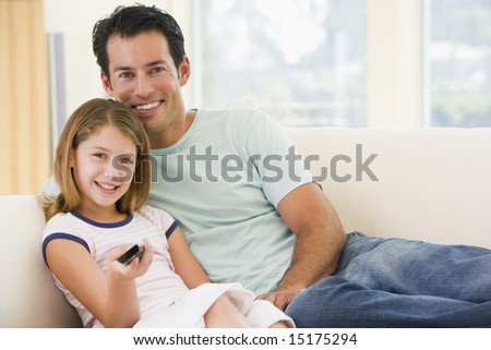 Man and young girl in living room with remote control smiling