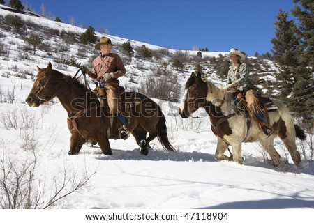Man and young woman riding horses in deep snow across a country landscape. Horizontal shot. - stock photo