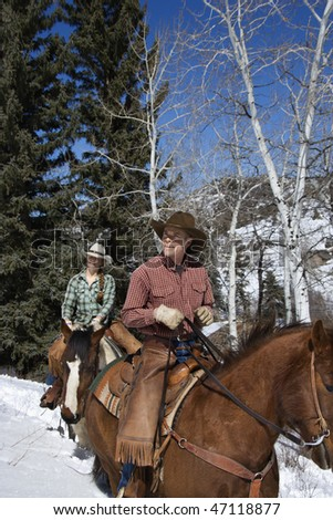 Man and young woman riding horses in the snow. Vertical shot. - stock photo