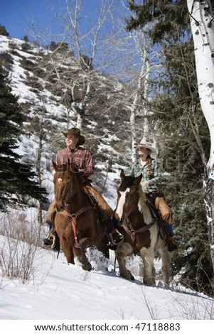 Man and young woman riding horses up a snowy hill on a country landscape Vertical shot. - stock photo
