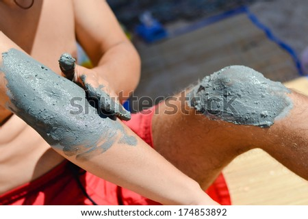 Man applying mineral blue mud on knee and elbow - stock photo
