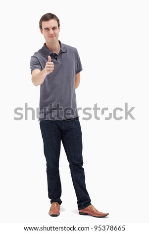Man approving with his thumb up against white background - stock photo
