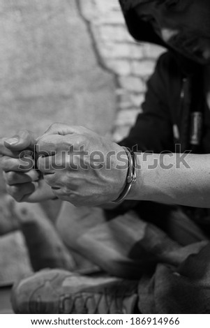 Man arrested and handcuffed suspect against the wall - stock photo