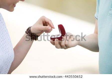 Man asking his beloved girlfriend to marry. Young female person taking the engagement ring out of the red box. Unrecognizable couple getting engaged. Concept image. Close-up of hands - stock photo