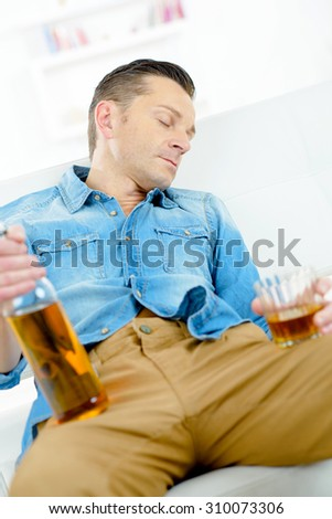 Man asleep with bottle and glass