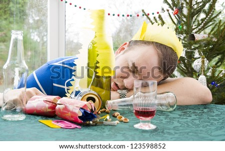 man asleep with head on table after christmas party - stock photo
