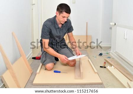 Man assembling a table at hone. - stock photo