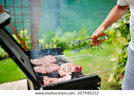 Man at a barbecue grill preparing meat for a garden party - stock photo