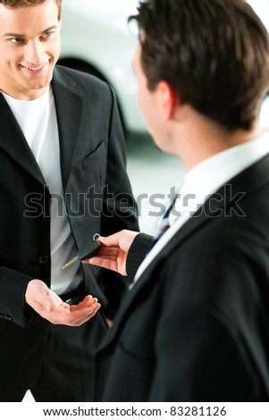 Man at a car dealership buying an auto, the sales rep giving him the key - stock photo