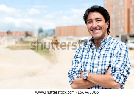 Man at a construction site looking very happy  - stock photo