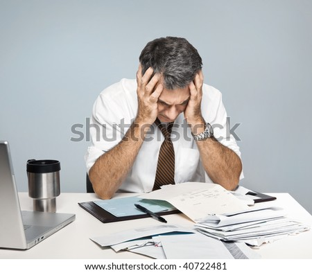 Man at desk in shirt and tie holding his head and worrying about money. - stock photo