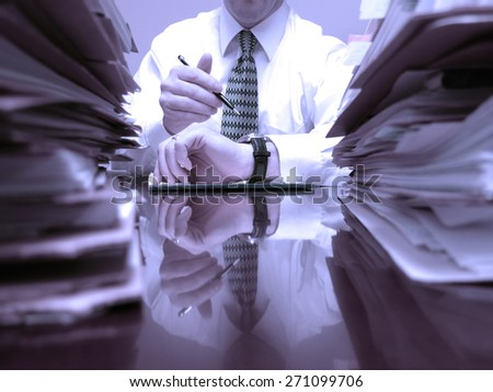 Man at desk with files piled high pointing to watch time urgency - stock photo
