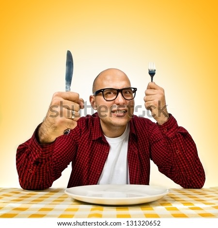 Man at dinner table with fork and knife raised. Hunger strike. - stock photo