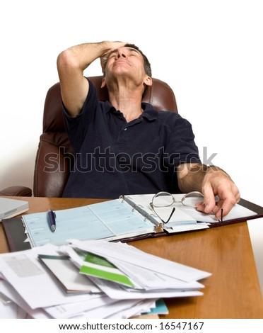 Man at his desk paying bills, too many bills. - stock photo