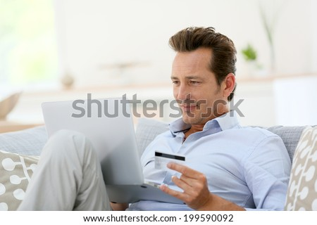 Man at home buying on internet - stock photo
