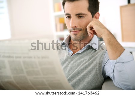 Man at home reading newspaper - stock photo