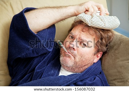 Man at home sick with the flu, taking his temmperature and holding an ice pack to his head.