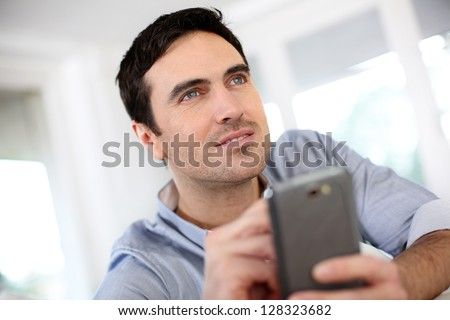 Man at home using smartphone - stock photo