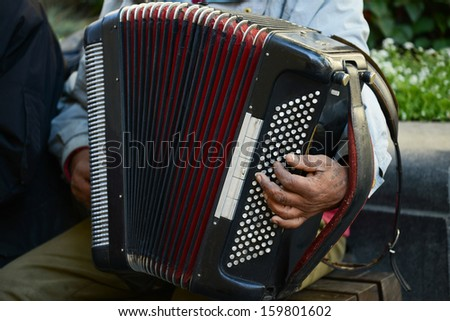 Man at street playing accordion - stock photo