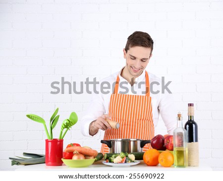 Man at table with different products and utensil in kitchen on white wall background - stock photo
