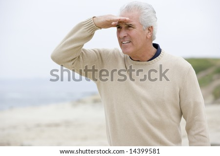 Man at the beach looking out with hand over eyes - stock photo