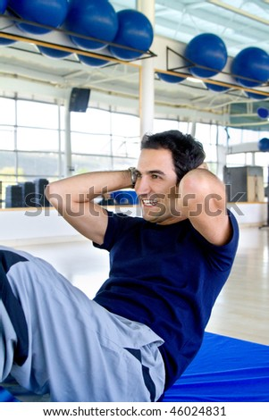 Man at the gym exercising his abs and smiling - stock photo