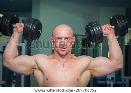 Man at the gym. Man makes exercises dumbbells. Sport, power, dumbbells, tension, exercise - the concept of a healthy lifestyle. Article about fitness and sports.