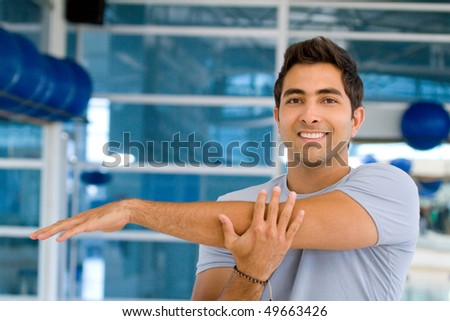 Man at the gym stretching his arm and smiling - stock photo