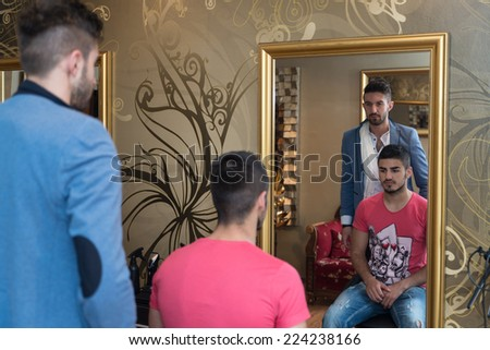 Man At The Hair Salon Situation - Handsome Young Hairdresser Giving A New Haircut To Male Customer At Parlor - stock photo