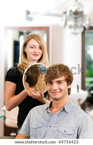 Man at the hairdresser, she has finished the cut and is showing the result in the mirror - stock photo