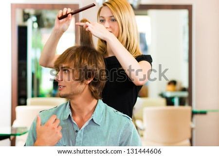 Man at the hairdresser, she is cutting his hair - stock photo