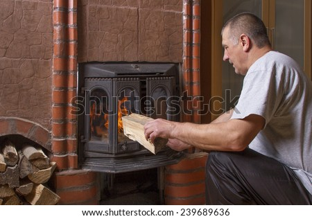 Man at the natural fireplace in house. - stock photo