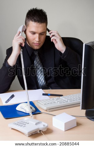 man at the office with two phones - stock photo