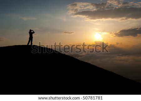 Man at the peak watching the sun