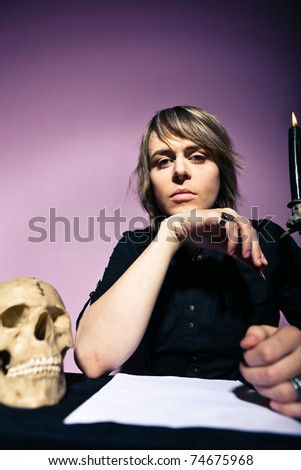 Man at the table with a candle and skull wrote a will - stock photo