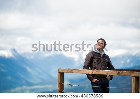 Man at view point in the mountains. Happy and smiling, looking to the sky. - stock photo