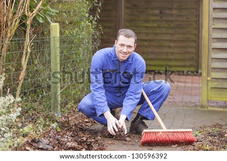 man at work.   groundskeeper (caretaker service) cleaning a garden path. - stock photo