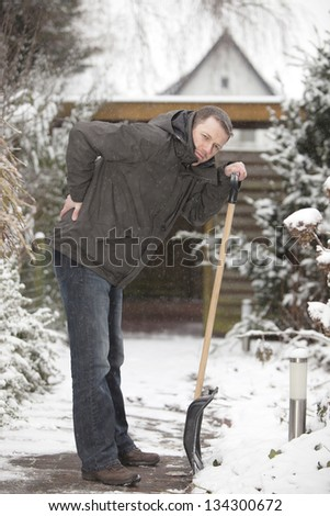 man at work. groundskeeper (caretaker service) removing snow with a shovel. having backache after hard work. - stock photo