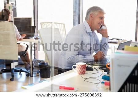 Man at work talking on phone, office interior - stock photo
