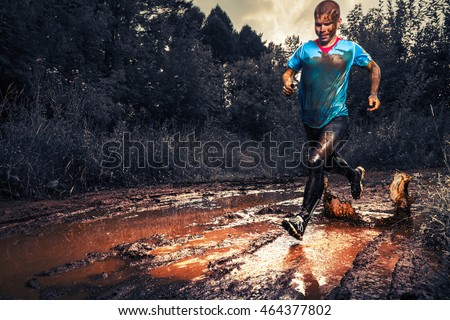 Man athlete running in the forest trail and crossing dirty puddle