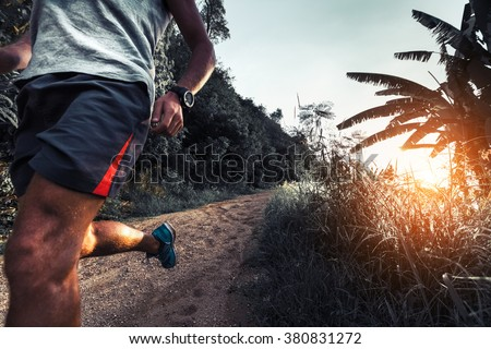 Man athlete running on the gravel road - stock photo